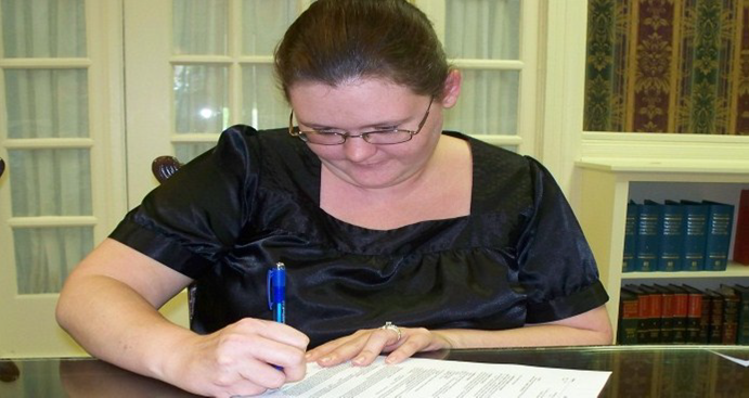 Angela B. signing the mortgage papers for her first home